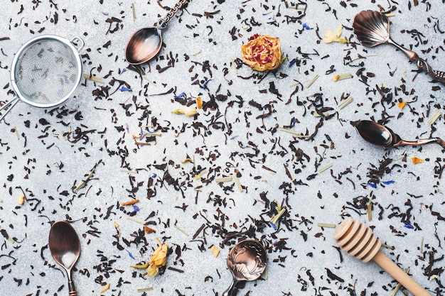 Tea leaves for brewing and spoons on a gray background. copy space. Premium Photo