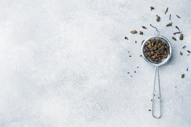 Tea leaves for brewing in a strainer on a gray background. copy space. Premium Photo