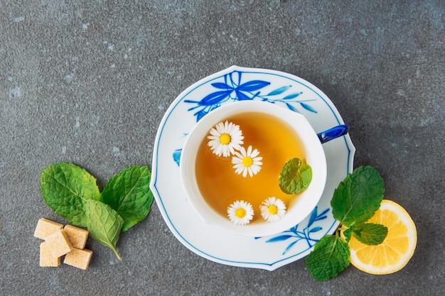 カップとソーサーにカモミールのお茶、レモン、ブラウンシュガーキューブ、緑の葉の灰色の漆喰の背景に平面図 無料写真
