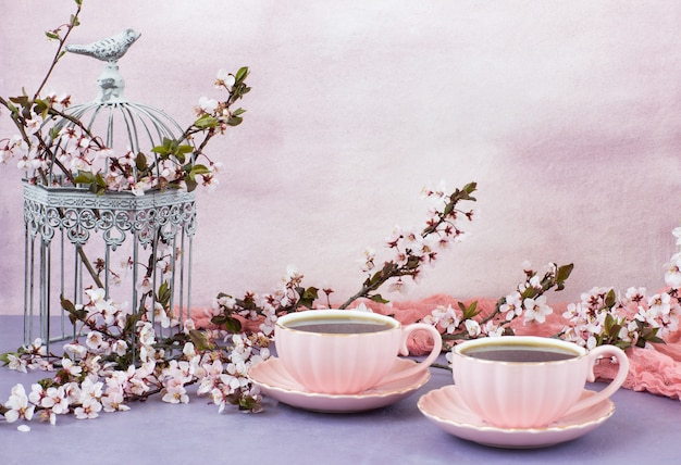 Tea in pink cups and cherry blossoms in a decorative cage Premium Photo