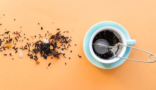 Tea preparing ceremony, mint green cup, tea-strainer and black fruit herbal dry tea on orange background. Premium Photo