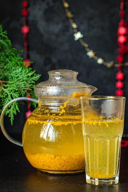 Чай из облепихи в чайнике и чашке на столе Premium Фотографии