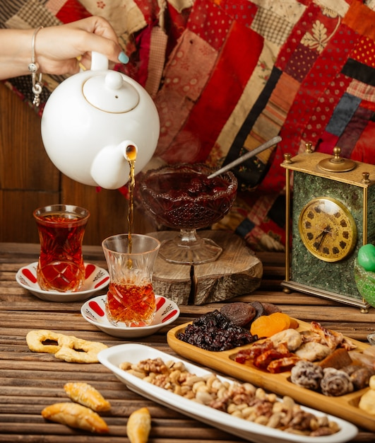 Tea set for 2 pax with dry fruits and sweets, white kettle, wooden table Free Photo