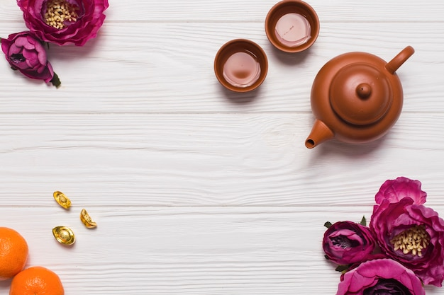 Tea set and flowers on wooden tabletop Free Photo