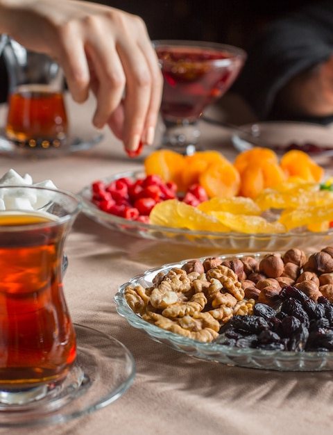 Tea setup with black tea in armudu glass with dried furits and nuts Free Photo