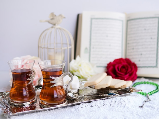 Tea and sweets on serving tray with opened quran in background Free Photo