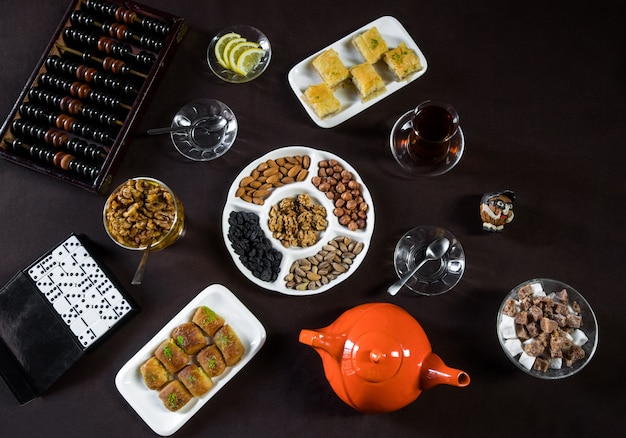 Tea table with tea glasses, nuts and gambling games. Free Photo