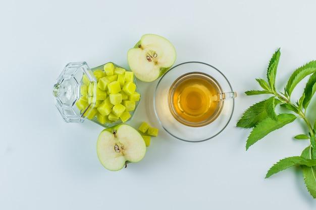 アップル、シュガーキューブ、白い背景のマグカップにハーブとお茶を置きます。 無料写真