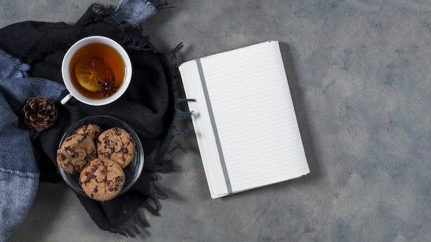 Tea with cookies on plaid near notebook Free Photo