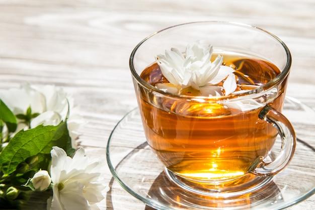 Чай с цветком на деревянном столе Premium Фотографии