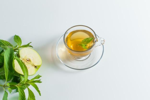ハーブとお茶、白い背景の上のマグカップにリンゴが横たわっていた。 無料写真