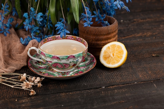 Tea with  lemon and bouquet of blue primroses on the table Free Photo