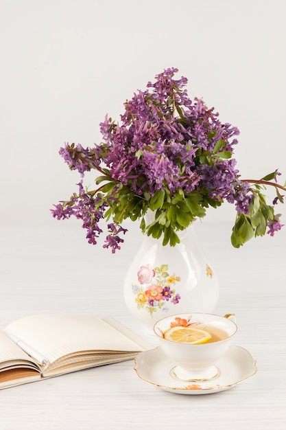 Tea with  lemon and bouquet of  lilac primroses on the table Free Photo