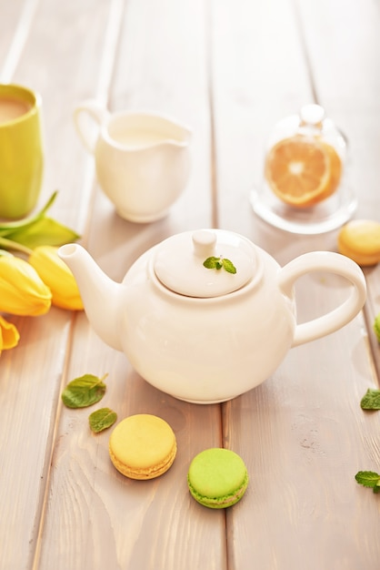 Tea with mint and lemon on the table with macaroons and yellow tulips Premium Photo