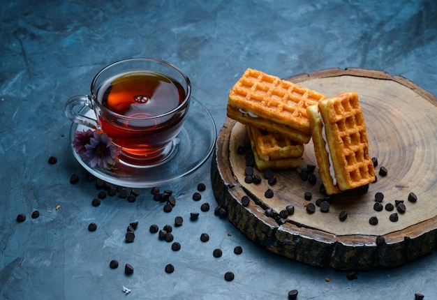 Tea with waffle, chocolate chips, flowers in a cup on blue and wooden board surface, high angle view. Free Photo