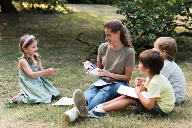 Учитель и дети, сидящие на траве Бесплатные Фотографии