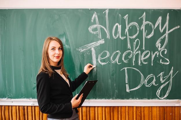 Teacher at blackboard with inscription Free Photo
