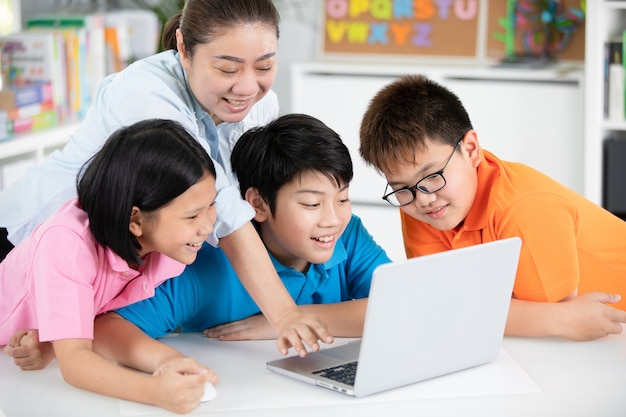 Teacher and cute asian children using laptop computer together ...