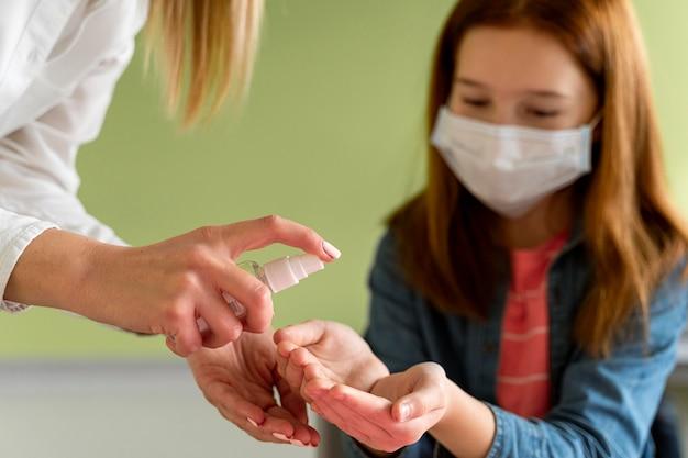 クラスで子供の手を消毒する先生 無料写真