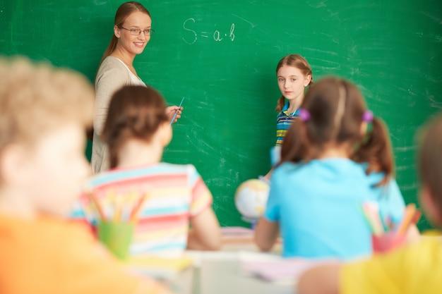 Teacher explaining arithmetic on the blackboard Free Photo