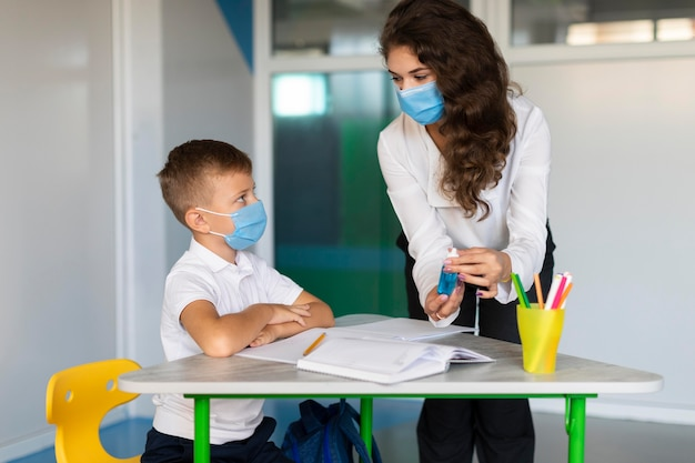 Teacher explaining the importance of disinfecting to a student Free Photo