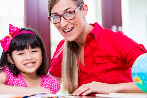 Teacher giving language lessons to chinese child Premium Photo