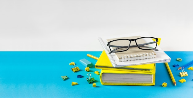 Teacher glasses, books and wooden letters on a blue table. school and teacher day concept. copy space. Premium Photo