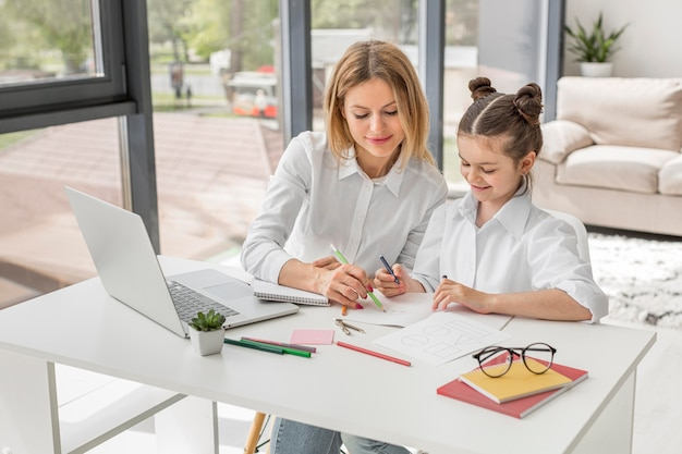 Teacher helping her daughter study at desk Free Photo