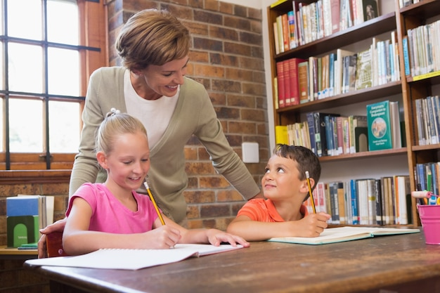 Teacher helping pupils in library Premium Photo