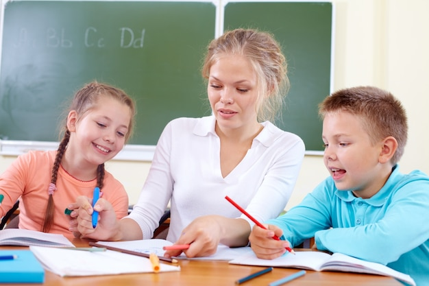 Teacher helping students in class Free Photo