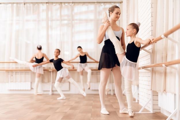 Teacher helps young ballerina near ballet bar. Premium Photo