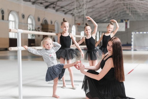 Teacher holding beginner's foot in hand at dance class Free Photo