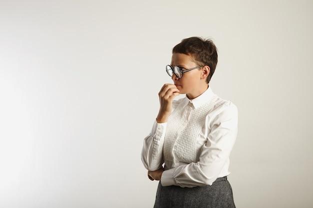 保守的な白とグレーの服装と白で隔離された思考の深い丸い黒眼鏡の先生 無料写真
