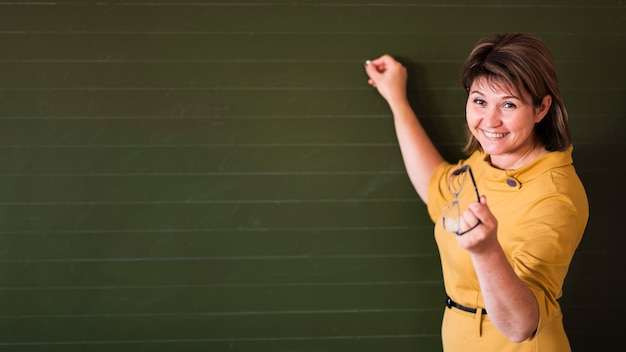 Teacher pointing at chalkboard with copy-space Free Photo