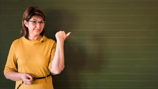 Insegnante che indica alla lavagna Foto Gratuite
