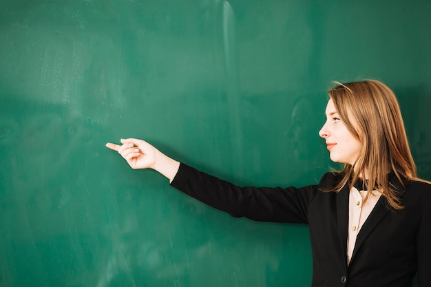 Teacher pointing finger to board Free Photo