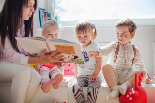 Teacher reading to preschoolers Premium Photo