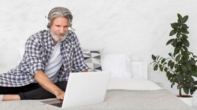 Insegnante che si siede sul letto facendo uso del computer portatile Foto Gratuite