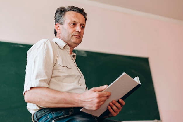 Teacher sitting with open textbook next a blackboard. Premium Photo
