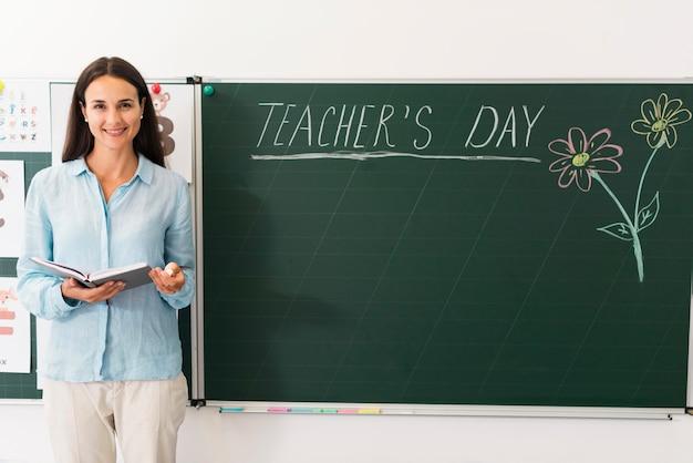 Insegnante in piedi accanto a una lavagna con copia spazio Foto Gratuite