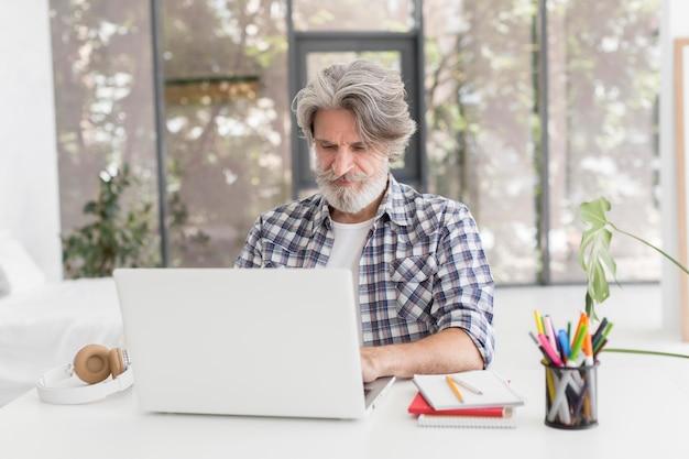 Учитель остается за столом, используя ноутбук Бесплатные Фотографии