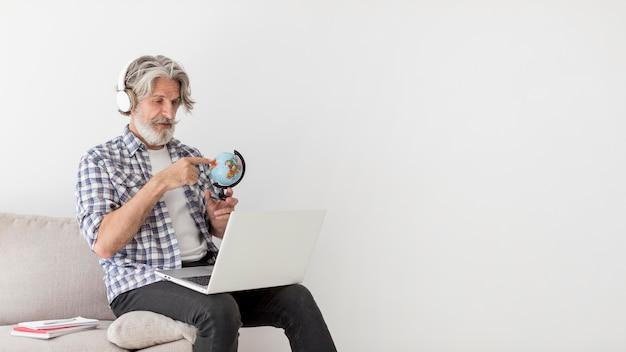 Insegnante che resta sullo strato che mostra il globo della terra al computer portatile Foto Gratuite