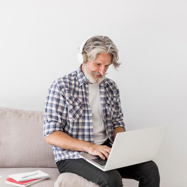 Insegnante stare sul divano con laptop Foto Gratuite