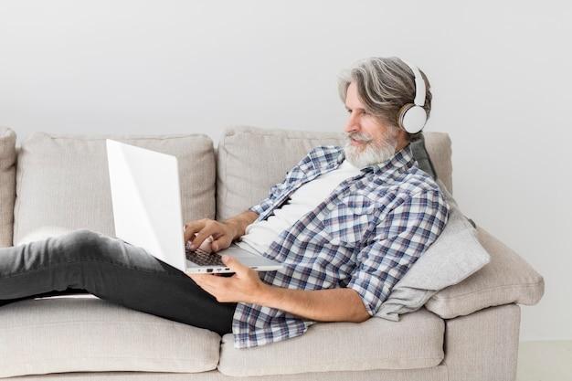 Insegnante stare sul divano con il portatile Foto Gratuite