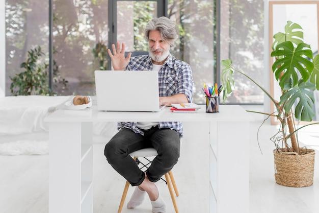 Insegnante che resta allo scrittorio che ondeggia al computer portatile Foto Gratuite