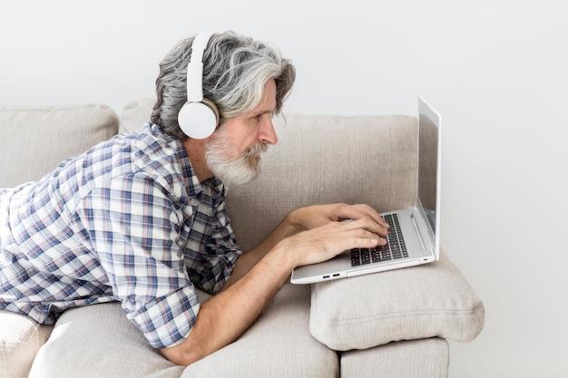 Учитель на диване с ноутбуком Бесплатные Фотографии