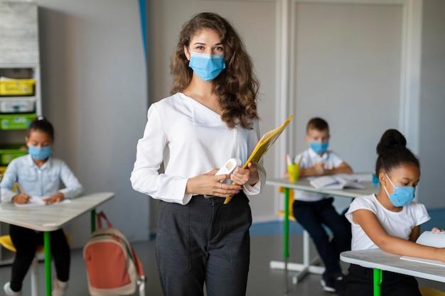 Insegnante e studente che indossano maschere facciali Foto Gratuite