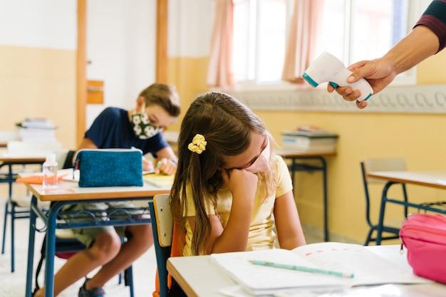 パンデミックの最中に体温計を使ってクラスで女の子の体温を測る先生。 Premium写真