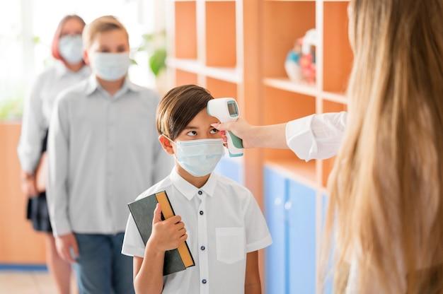 Insegnante che misura la temperatura corporea a scuola Foto Gratuite
