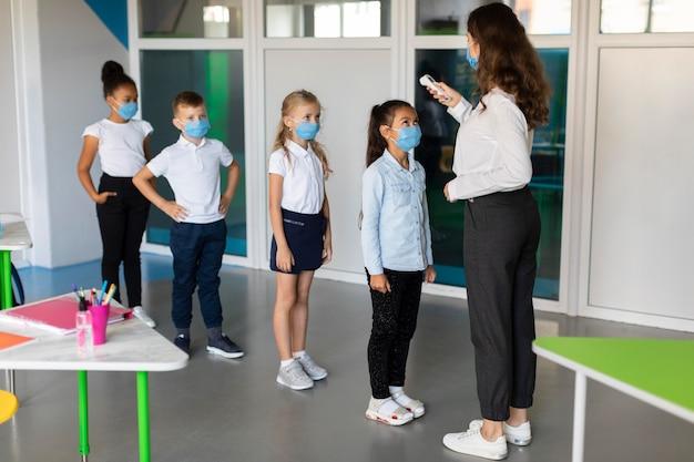 Insegnante che misura la temperatura dei suoi studenti Foto Gratuite